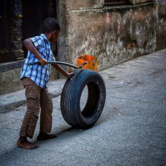 fine art print boy playing with a tire stone town zanzibar tanzania